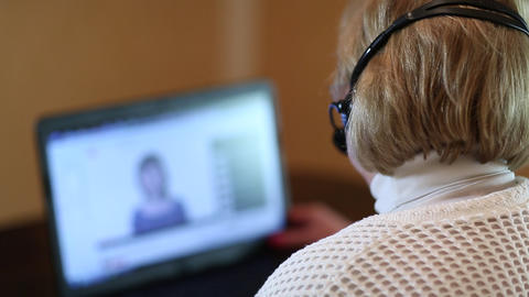 Woman with headphones with microphone talks to a customer on computer Footage