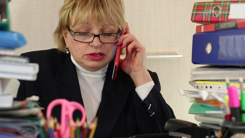 Senior woman chief accountant in glasses and with red smartphone sits at the tab Live Action