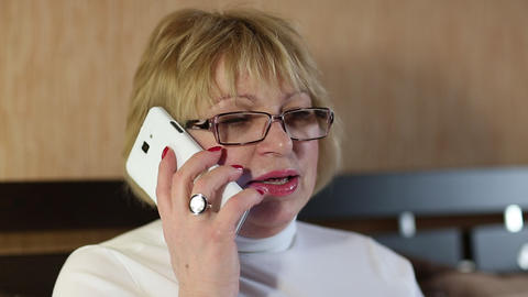 Senior woman in glasses with smartphone speaks smiling, laughs and gesticulates Footage