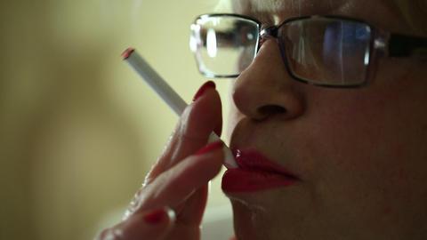 Senior woman smoking a cigarette Live Action