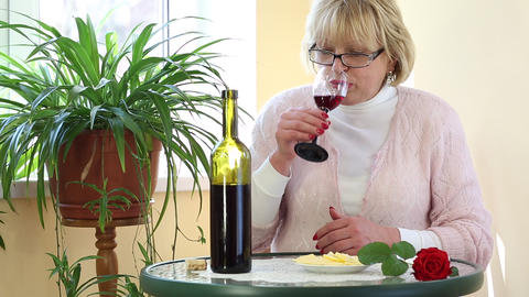 Woman sits at a table drinking wine and eating cheese Footage