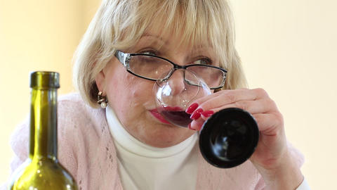 Woman drinking wine. Depressed senior woman with bottle of wine Footage