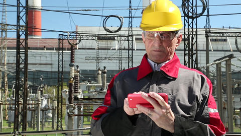 Power engineering specialist with red smartphone at electropower station Live Action