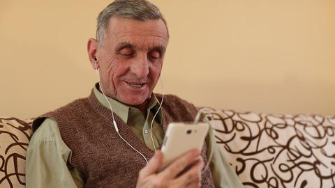 Senior man communicates through a smartphone. Man with mobile phone Footage