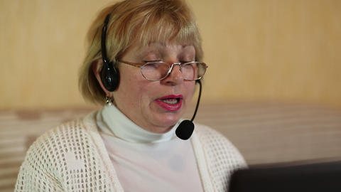 Woman with headphones with microphone talks to a customer via computer Footage