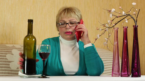 Woman sits at the table, drinks red wine and speaks on smartphone Footage