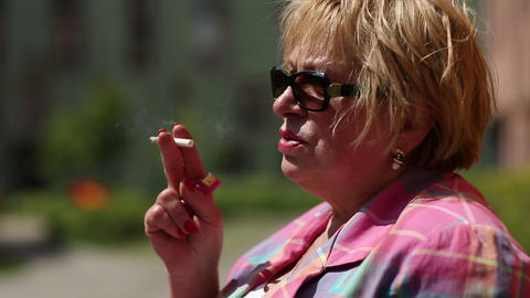 Senior woman with glasses smoking a cigarette Footage