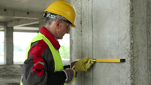 Worker in yellow hard hat with level on the building site Footage
