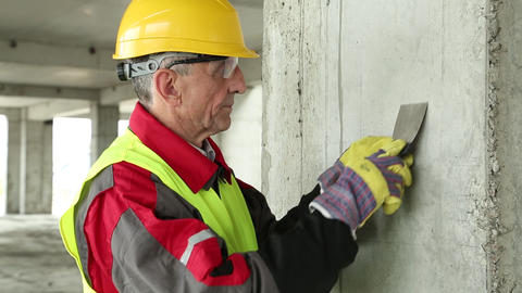 Worker with putty knife on the project site Footage