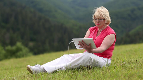 Woman sits on the grass and uses tablet PC Live Action