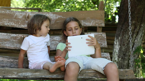 Two girls with tablet computer sit on the swing bench Footage