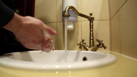 Man washes his hands in the sink, turns on rare valve, picks soap Footage