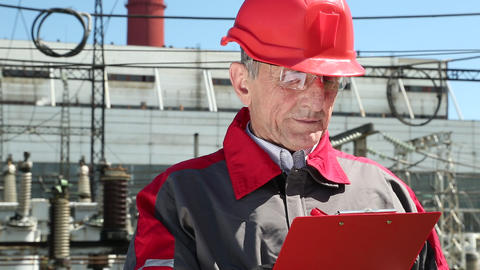Engineer builder in red helmet writes down information about object Footage
