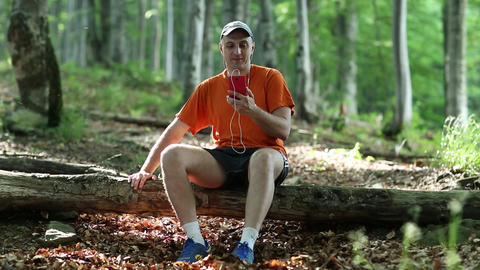 Man sitting on log, talking on skype, smiling and waving hand Footage
