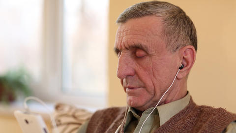 Senior man with white smartphone sits on the couch and listening to music Footage