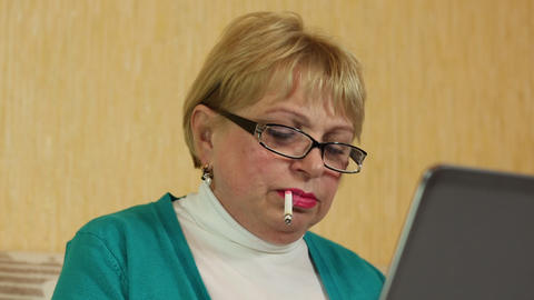 Woman in glasses types text using laptop and smoking a cigarette Footage