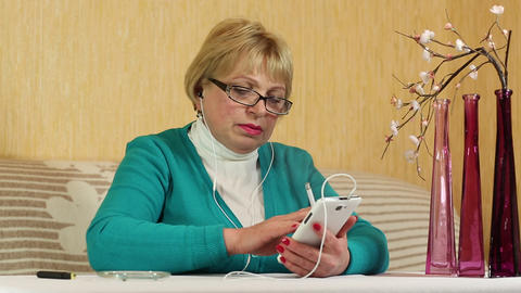 Woman in glasses with white smartphone sits at a table and smoking a cigarette Footage
