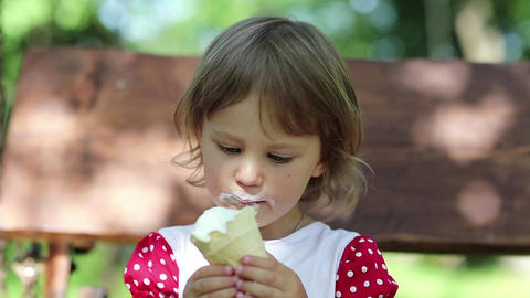 Little girl sits on the bench and eats ice cream Footage