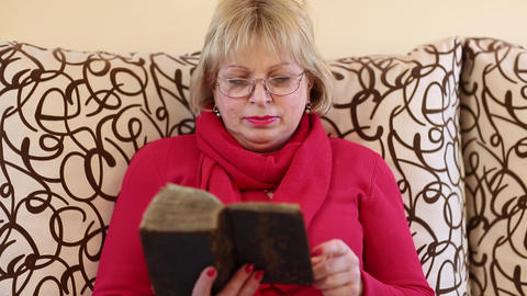 Woman sitting on a divan and reading old book Footage