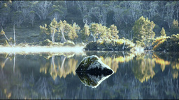 morning mist on calm lake with rock Footage