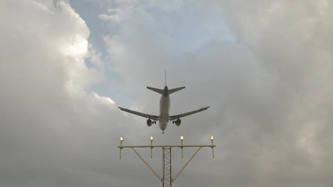 Aircraft landing with airport landing lights and cloudy sky Footage