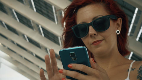 Tattooed Woman Using His Smart Phone With A Big Solar Panel 4k UHD Shot stock footage