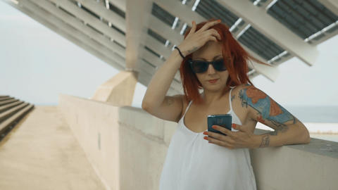 Red Head And Tattooed Woman Using His Smart Phone In The Street stock footage