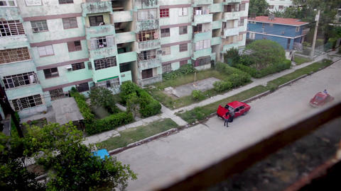 2 people having a look at the old red car engine in a La Habana neighborhood Footage