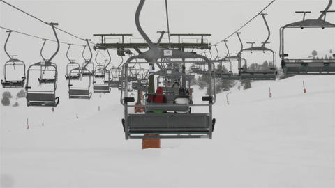 Ski lift with skiers while snowing Footage