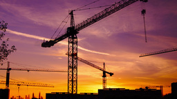 Time lapse cranes working in construction site at dusk, zoom in Footage