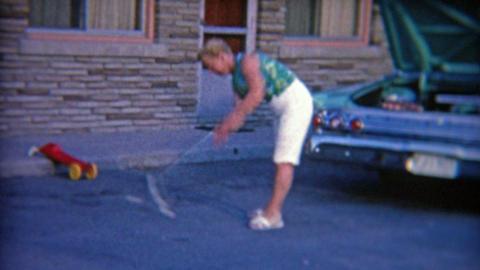 1964: Women hitting golf balls off the asphalt pavement from hotel parking lot Footage