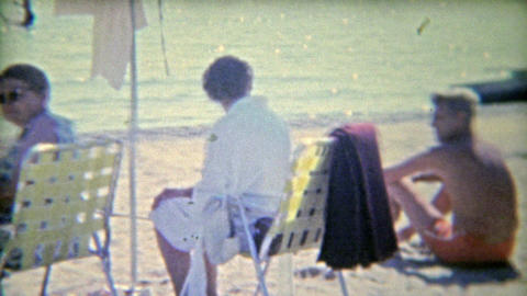 1961: Family relaxing at the beach on a hot sunny day Footage