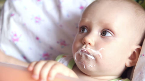 Eight month girl eating baby food Live Action