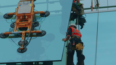 Close-up shot of group of builders securing a glass panel in place Live Action