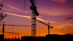Time Lapse Cranes Working In Construction Site At Dusk, Pan.Craner Climbing stock footage