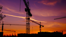 Time lapse cranes working in construction site at dusk, zoom out.Craner climbing Footage