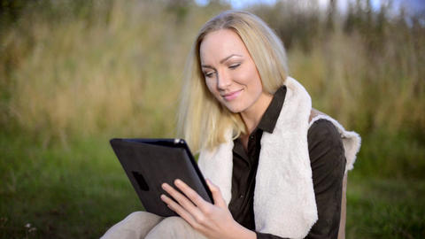 Attractive young woman using tablet computer outside. Medium Shot Live Action