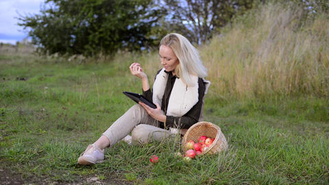 Young woman eats fresh apple outdoor and watching movie on tablet Footage