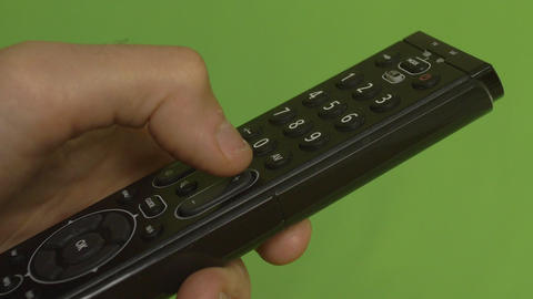 Male hand changing channels with remote control on a green screen sideshot Footage