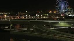 有明高速の立体交差をライトを点し行き交う車と観覧車 Footage