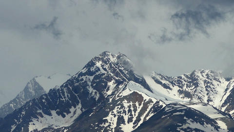 snow-capped mountain peaks among the clouds Footage