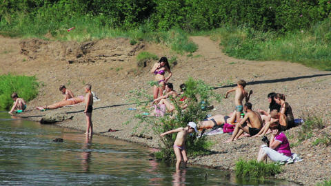 People sunbathe on the beach of Siberian river Stock Video Footage