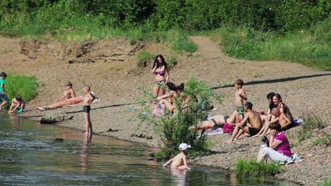People sunbathe on the beach of Siberian river Stock Video Footage