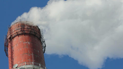factory chimney with smoke under blue sky - timela Stock Video Footage