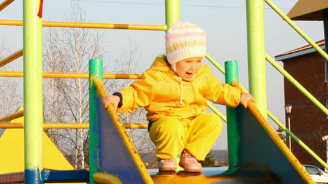 cute little girl in yellow on slide Stock Video Footage