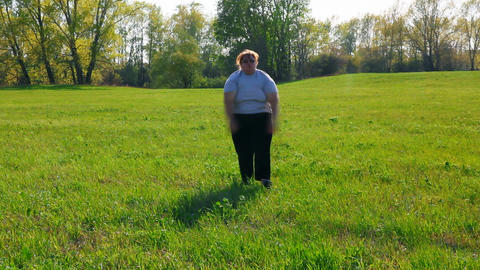 sport - overweight woman exercising on green meado Stock Video Footage