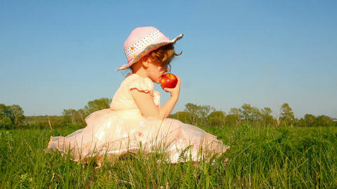 little girl eating apple on meadow Stock Video Footage