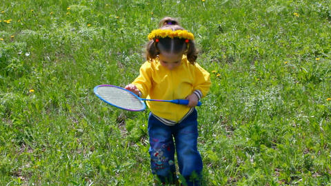 little girl playing badminton on spring meadow Stock Video Footage