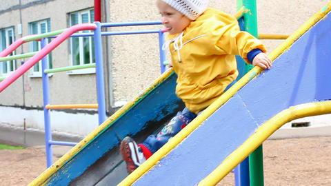 cute little girl in yellow on slide - slow motion Stock Video Footage