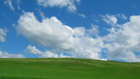 green hill with grass under cloudy sky - timelapse Stock Video Footage
